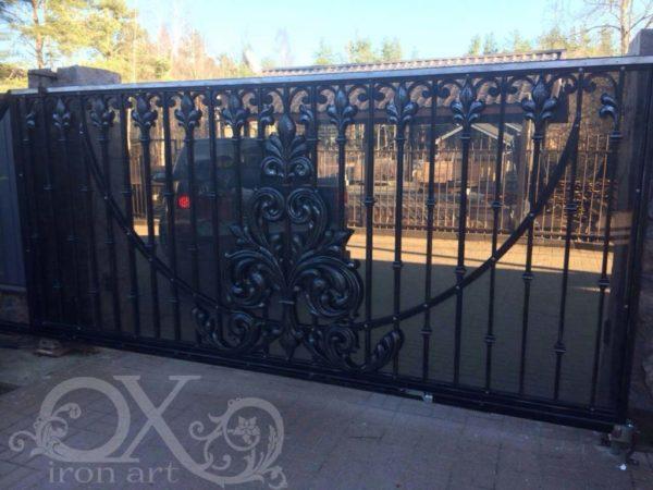 Een bijzondere poort, deze PR0019016. Een klassiek ogende poort die geen twee draaiende poortdelen heeft, maar één schuivende poort. Bovendien wilde de eigenaar dat de poort afgedicht was, maar toch doorzichtig. Dit laatste is namelijk heel praktisch tegen zwerfvuil. Als geheel moest de poort er natuurlijk onverminderd fraai uit komen te zien. De decoratieve smeedijzeren elementen dragen belangrijk bij aan de esthetische waarde waar deze klant naar op zoek was. Het is een uniek ontwerp geworden, dat speciaal voor deze klant met liefde en aandacht door ons is gemaakt. Over deze poort Deze smeedijzeren afgedichte schuifpoort-toegangspoort PR 0019016 bestaat uit een centrale schuifdeur en twee loopdeuren. Doordat de poort schuift is er ruimte minder nodig. Je ziet meteen dat deze poort sierlijk gevormd smeedwerk heeft. De staven waarop het smeedwerk van de centrale schuifdeur is vastgezet, hebben een versiering in tulpvorm aan de bovenkant. Deze versiering komt terug in de versieringen bovenaan en onderaan de loopdeuren. Leuk detail: ze komen zelfs terug in de bolle lampen die boven op de stenen muren staan. De dwarsstaaf die voor extra stevigheid van de centrale schuifdeur zorgt, is uitgevoerd in een halve cirkel, perfect aansluitend op het sierlijke gebogen design. De afdichting tenslotte is gerealiseerd in getint plexiglas. Gebruiksvriendelijk en praktisch Natuurlijk is deze poort voorzien van afstandsbediening en aangesloten op de beveiligingssystemen. Door de loopdeur hoef je niet altijd gebruik te maken van de grote schuifpoort. Bij veel dagelijkse bewegingen, lopend of met de fiets, is dit wel zo praktisch. Prijsindicatie De schuifpoort zoals deze hier is geleverd kent een investering vanaf 8.000 euro. Je hebt dan een zware poort van 4 meter breed en 1.80 meter hoog. Maar er zijn veel meer uitvoeringen mogelijk. Denk aan een afdichting met (rook)glas, of met volledig dichte platen van staal, het mooi roestende Cortenstaal of met bewerkt hout. Gewoon openlaten ka